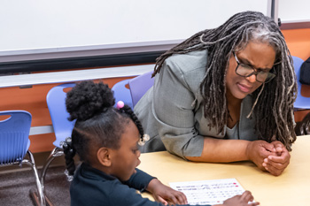 South Avondale kindergartner NaDavia reviews her sounds and letters with Rev. Connie, who promised to visit her class in first grade this school year. (Photo: Larry Pytlinski)
